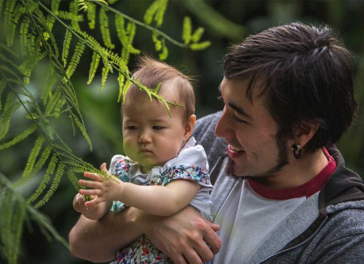 Father holding baby looking at a tree branch in the Rainforest Biome